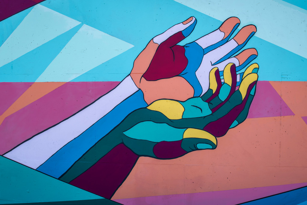multi-coloured hands painted on a wall